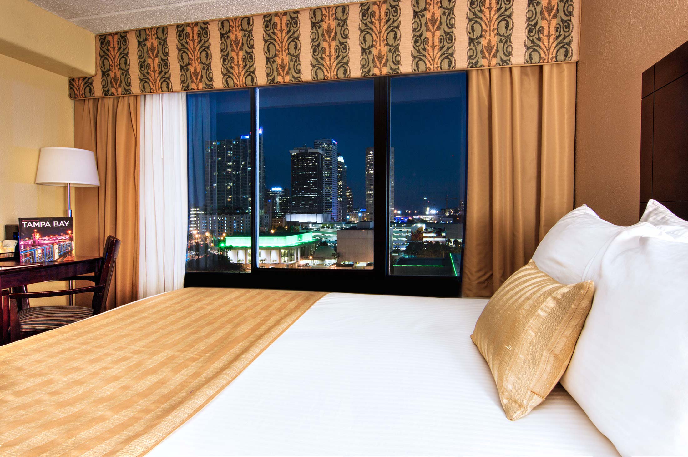 single king guest room with night view of the city