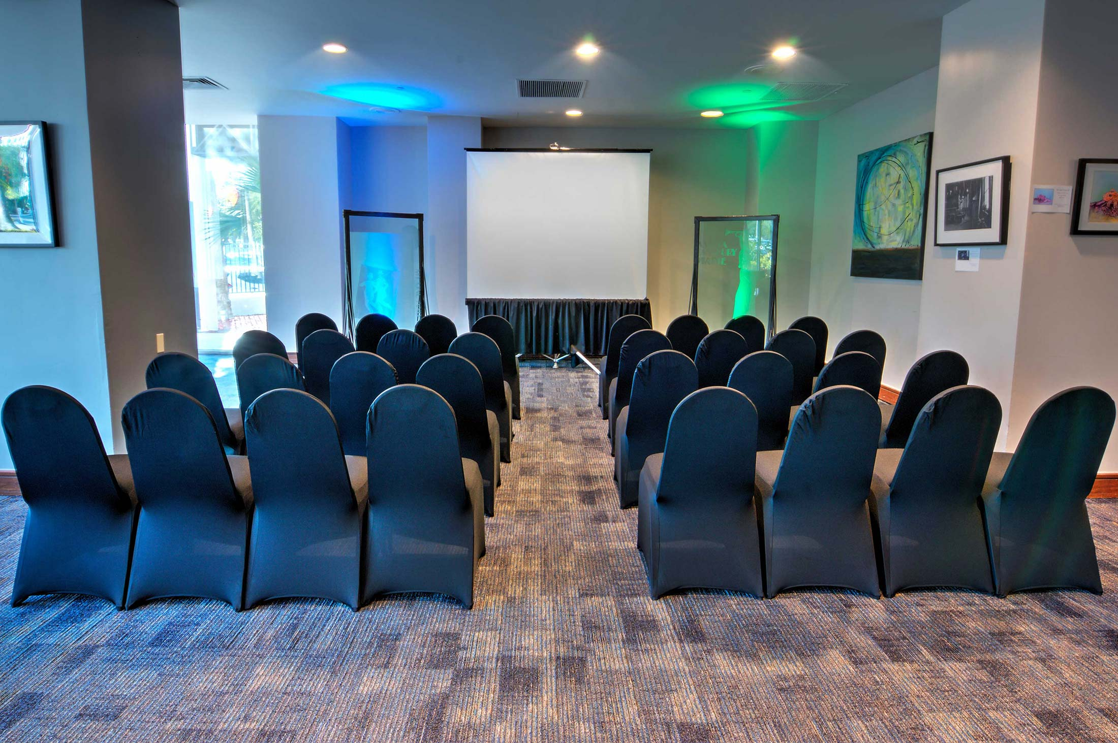 small theatre meeting arrangement with black chairs and projector screen