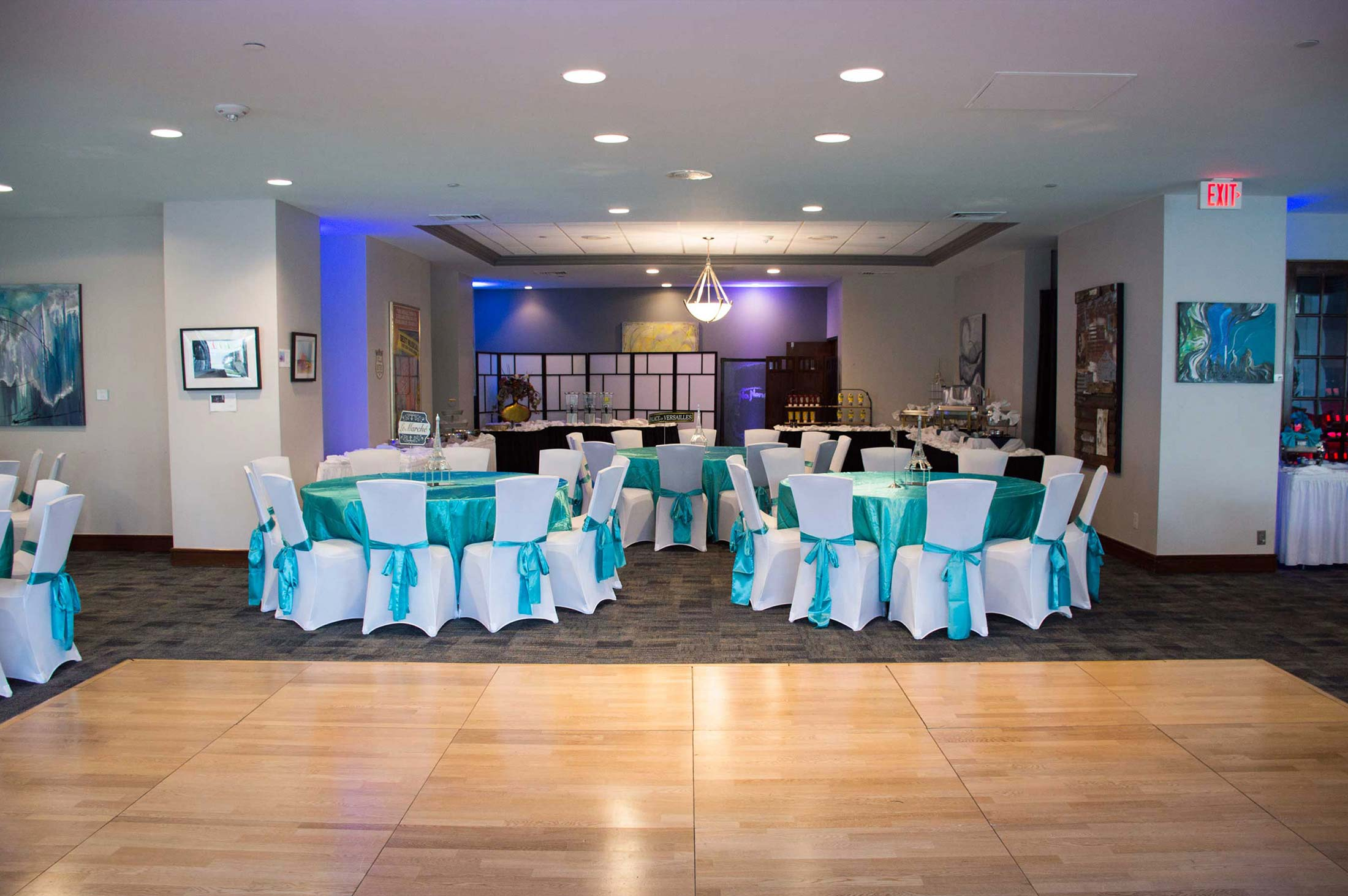 banquet set up with rounds with teal bows on chairs
